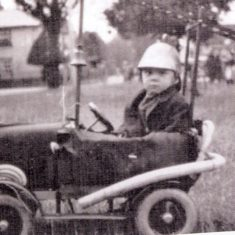 Don Hills in his pedal car made to look like a fire engine with ladder and hose in the 1930 carnival.